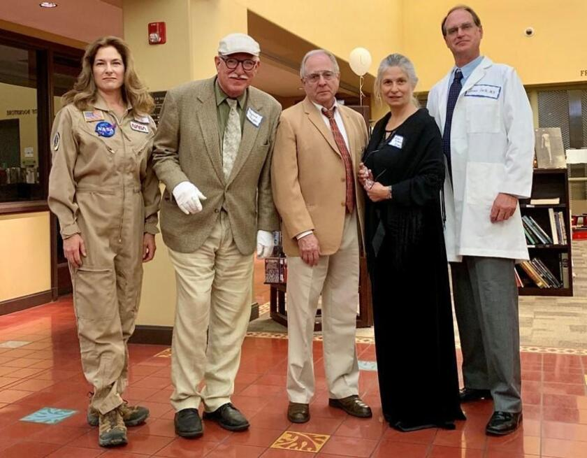 """Actors portraying Sally Ride (Wendy Hovland-Henry), Raymond Chandler (Tim West), Theodor Geisel (JMarcus Newman), Ellen Browning Scripps (Betty Matthews) and Jonas Salk (John Tessmer) take part in """"The Caper on Draper,"""" a whodunnit mystery held June 6, 2019 at La Jolla Library."""