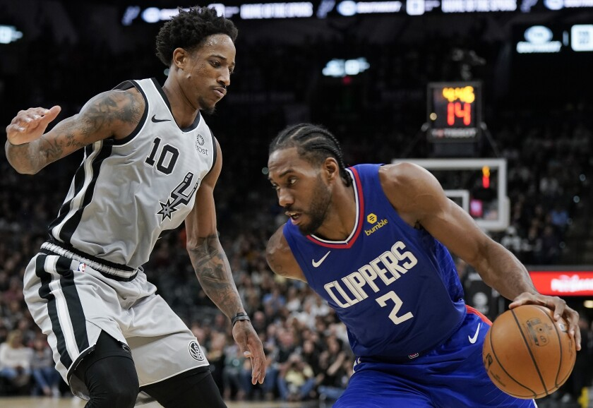 Clippers forward Kawhi Leonard tries to drive past Spurs guard DeMar DeRozan during the first half of a game Dec. 21, 2019, in San Antonio.