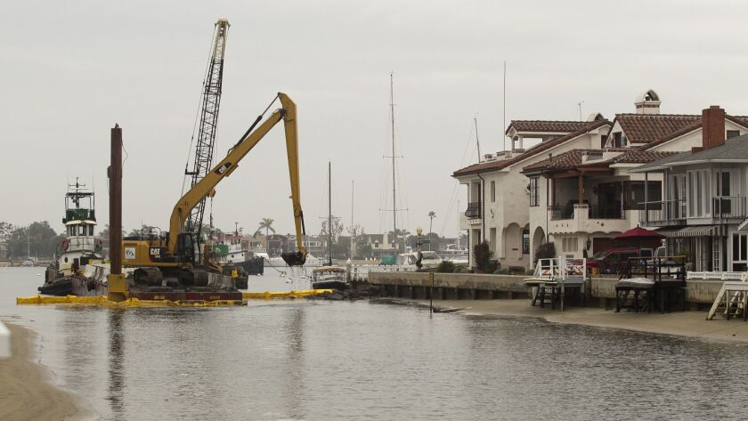 An excavator's scoops a bucket filled with soil from the Grand Canal between Balboa Island and Littl