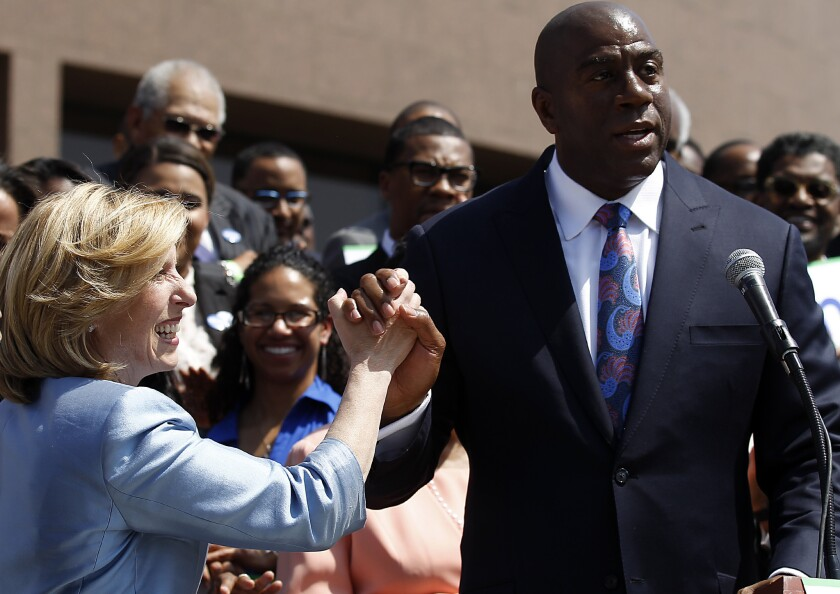 Former Lakers great and current Dodgers executive Magic Johnson gives Wendy Greuel a high-five after endorsing her campaign to be mayor of Los Angeles.