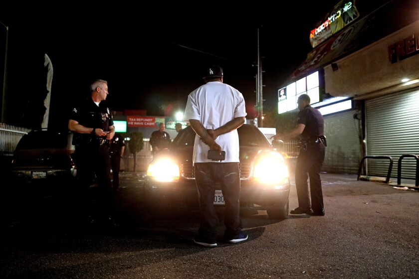 LAPD Metropolitan Division officers Mike Burtner, left, and Erick Sinkovits detain a suspect.