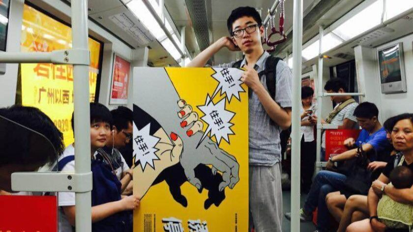 A feminist activist carries an anti-sexual harassment poster on the Guangzhou subway. (Photo courtes