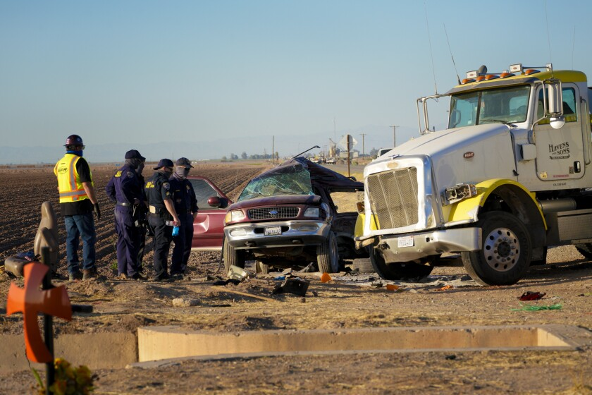 Investigators look over the scene of a deadly crash involving an overloaded SUV and a big rig