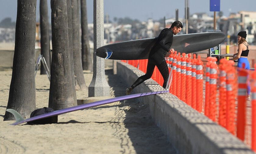 A surfer walks past a barrier to the sand in Newport Beach on Saturday.
