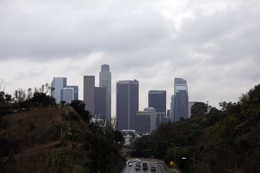 Clouds surround the downtown Los Angeles skyline as seen above the 110 Freeway.