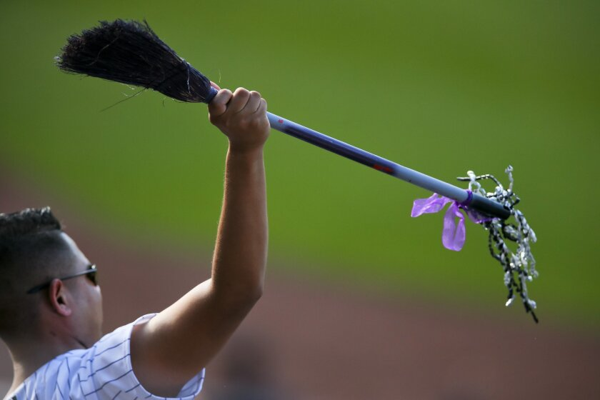 A Rockies fan holds up a broom as Colorado swept the Dodgers on Sunday.
