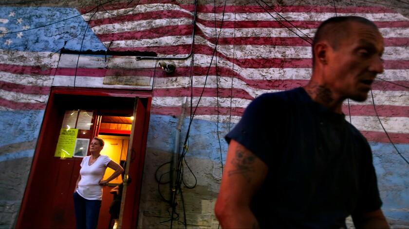 Danny Hinkie, 44, walks past Bentley's Place in north Philadelphia.