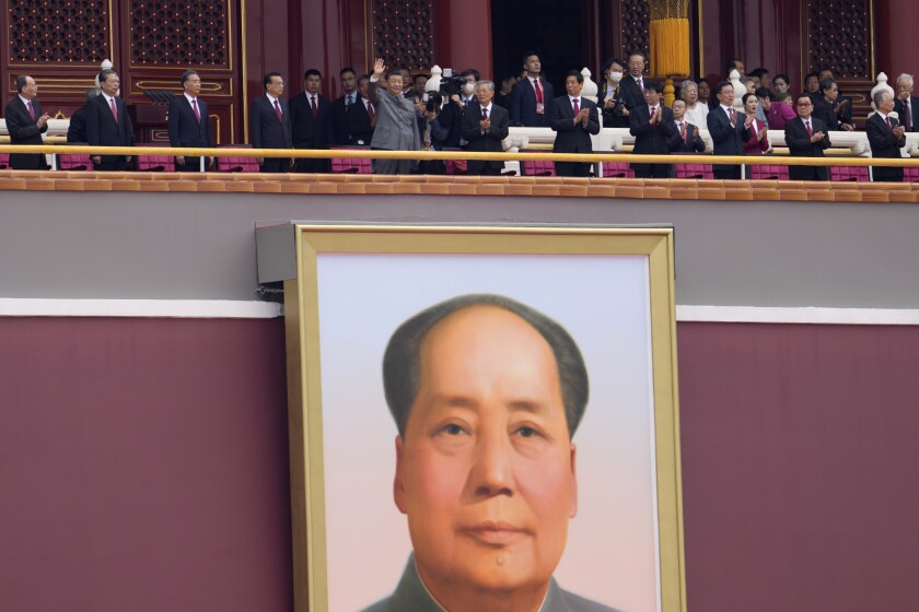 Chinese President Xi Jinping, center, waves above a large portrait of the late leader Mao Zedong during a ceremony to mark the 100th anniversary of the founding of the ruling Chinese Communist Party at Tiananmen Gate in Beijing Thursday, July 1, 2021. Artillery roared, bands played and fighter jets soared overhead as thousands gathered in Beijing's iconic Tiananmen Square for a ceremony marking the centenary of the ruling Communist Party. Meanwhile, Hong Kong held its own annual commemorations of the 1997 handover from British to Chinese rule, given added significance by the party centenary and the arrests of political activists and journalists under a sweeping national security law imposed last year. (AP Photo/Ng Han Guan)