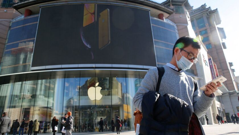 A man uses his smartphone outside an Apple store in Beijing.