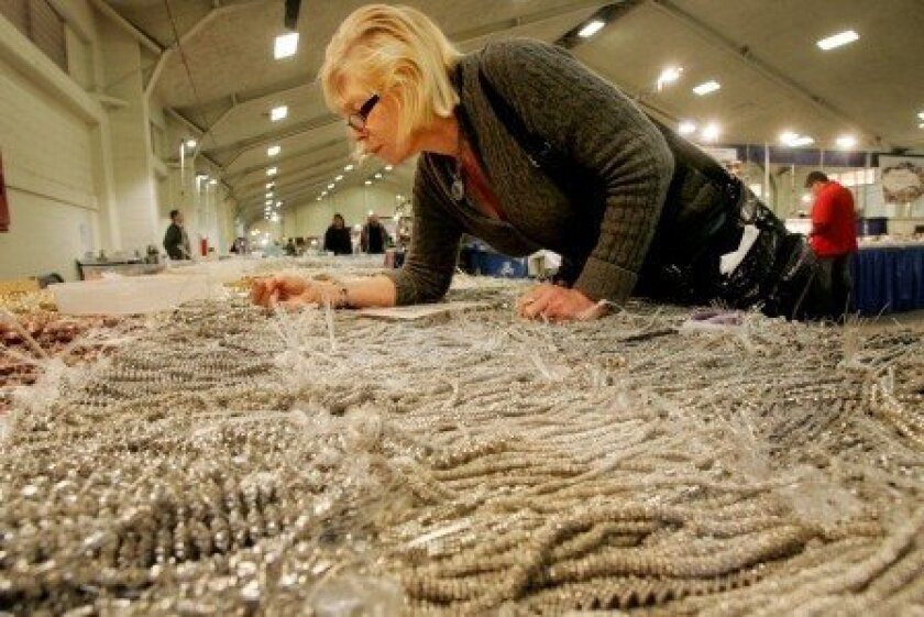 Linda Taylor looks over strands of pewter beads at last year's Gem Faire at the Del Mar Fairgrounds.
