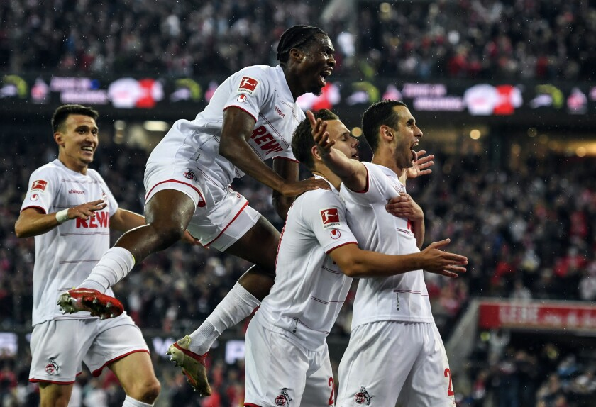Cologne's Ellyes Skhiri, right, celebrates with teammates after scoring his side's third goal of the game during the German Bundesliga soccer match between 1. FC Cologne and SpVgg Greuther Fuerth at the RheinEnergieStadion in Cologne, Germnay, Friday, Oct. 1, 2021. (Marius Becker/dpa via AP)