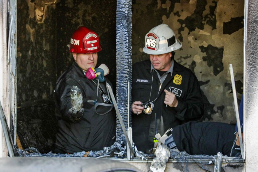 Two LAFD arson investigators examine a charred room at the Venice Hotel.