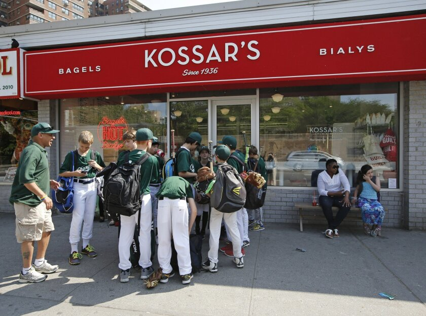 A baseball team gathers outside Kossar's Bagels and Bialys store, Thursday, May 26, 2016, on Manhattan's Lower East Side in New York. A bagel contains malt or some form of sugar. Bialys have no sugar. Bagels are more dense and are boiled. Bialys go straight into the oven. Bialys are flatter and oft