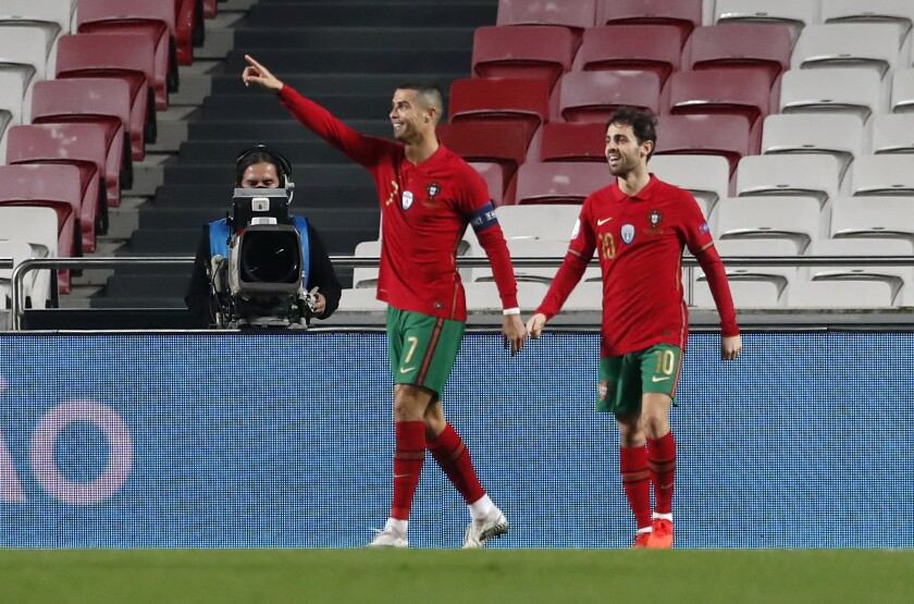 Cristiano Ronaldo (izquierda), de la selección de Portugal, es felicitado por su compañero Bernardo Silva tras anotar ante Andorra, el miércoles 11 de noviembre de 2020 (AP Foto/Armando Franca)