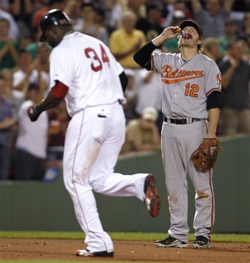 Baltimore Orioles third baseman Mark Reynolds eats sunflower seeds as Boston Red Sox's David Ortiz rounds the bases with the first of three home runs in a row by the Red Sox during the seventh inning of a baseball game at Fenway Park in Boston on Thursday, July 7, 2011. (AP Photo/Winslow Townson)