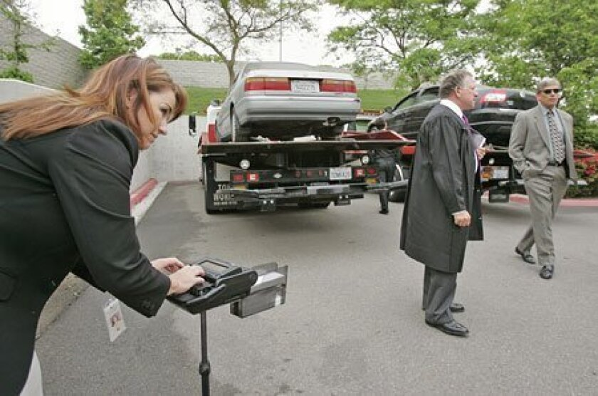 Court reporter Lisa Meyers (left) worked in the parking lot at the Vista courthouse during a hearing Friday, where cars in a road-rage case were inspected by Judge Harry Elias (center) and prosecutor Jeff Dusek (right).  (Charlie Neuman / Union-Tribune)