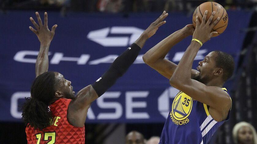 Golden State Warriors forward Kevin Durant (35) shoots against Atlanta Hawks forward Taurean Prince (12) during the first half.