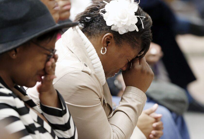 Danielle Burns, hermana de Jamar Clark, derecha, llora acompañada de otros familiares durante una conferencia de prensa organizada por la Liga Urbana de Minneápolis, en Minneápolis, Minnesota. Jamar Clark murió el domingo por disparos de un policía de Minneápolis durante un aparente enfrentamiento.