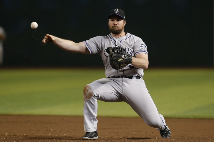 FILE - In this Monday, Aug. 19, 2019, file photo, Colorado Rockies first baseman Daniel Murphy makes a play for an out on a ball hit by Arizona Diamondbacks' Jarrod Dyson in the third inning during a baseball game in Phoenix. Colorado Rockies general manager Jeff Bridich says veteran first baseman Daniel Murphy may have rushed back too soon from a broken left index finger last season. (AP Photo/Rick Scuteri, File)