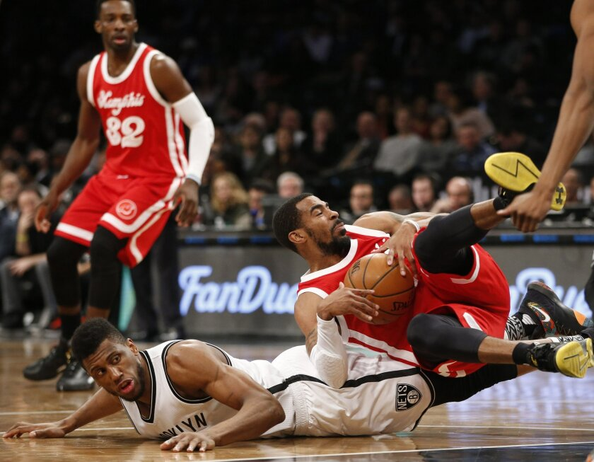 Memphis Grizzlies guard Mike Conley tumbles over Brooklyn Nets forward Thaddeus Young while grabbing a loose ball during the first half of an NBA basketball game Wednesday, Feb. 10, 2016, in New York. (AP Photo/Kathy Willens)