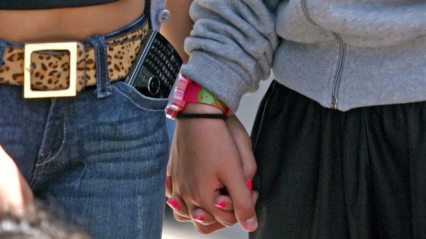 Vanessa Palacios, left, and Eva Estrella, both 16 and sophomores, holds hands as they participate in