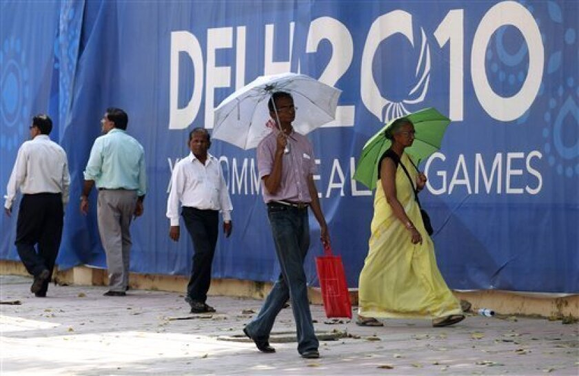 People walk past a hoarding outside the Jawaharlal Nehru stadium, the main venue of the Commonwealth Games, in New Delhi, India, Friday, Oct. 1, 2010. The Commonwealth Games are scheduled to begin on Sunday. (AP Photo/Anja Niedringhaus)