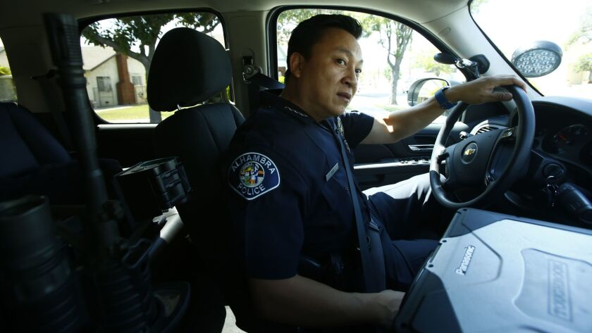 """Police Chief Timothy Vu, driving through Alhambra, was named the city's police chief in April. """"Ninety-five percent of this job is just talking to people,"""" said Vu, 46. """"The best thing we can do is get out of our car and explain."""""""