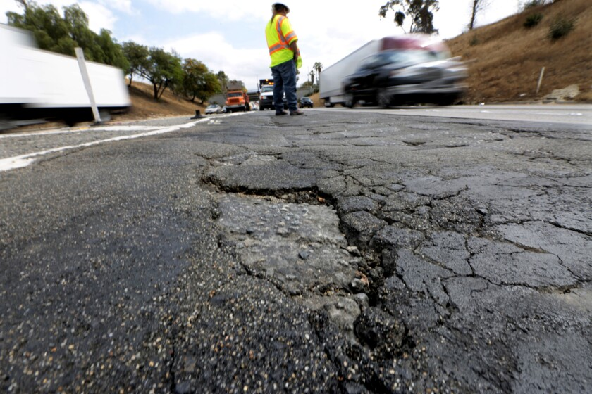 A Caltrans maintenance supervisor stands near the junction of the 5 and 60 freeways in L.A., where there are numerous potholes and large cracks in the roadway.