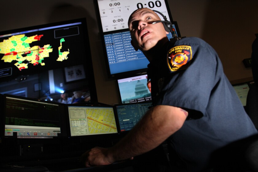 Dispatcher Tony Porrata turns to talk to another dispatcher about a call at the Los Angeles Fire Department Dispatch Center.