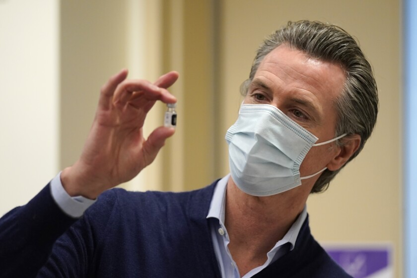 Gov. Gavin Newsom holds a vaccine vial on at Kaiser Permanente Los Angeles Medical Center