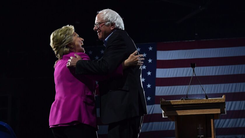 Democratic presidential nominee Hillary Clinton and Vermont Sen. Bernie Sanders embrace during a campaign rally in Raleigh, N.C., on Thursday.