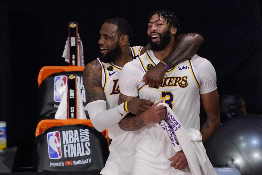 FILE - Los Angeles Lakers' LeBron James, rear, and Anthony Davis (3) celebrate after the Lakers defeated the Miami Heat 106-93 in Game 6 of basketball's NBA Finals in Lake Buena Vista, Fla., in this Oct. 11, 2020, file photo. Anthony Davis is finalizing a five-year contract worth up to $190 million to return to the Los Angeles Lakers. Davis' agent, Rich Paul of Klutch Sports, confirmed the terms of Davis' pending free agent deal to The Associated Press on Thursday, Dec. 3, 2020. One day after LeBron James agreed to a two-year, $85 million contract extension with the Lakers through 2022-23, Davis committed to the Lakers through the 2024-25 season. (AP Photo/Mark J. Terrill, File)