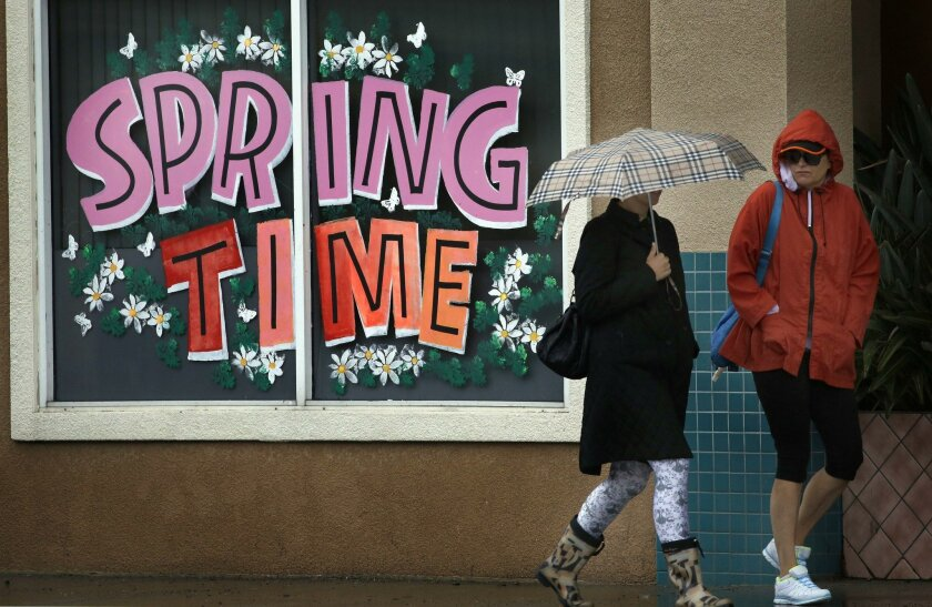 In this file photo, people walked through the rain past a Mission Hills storefront as a spring storm moved through the region in May.