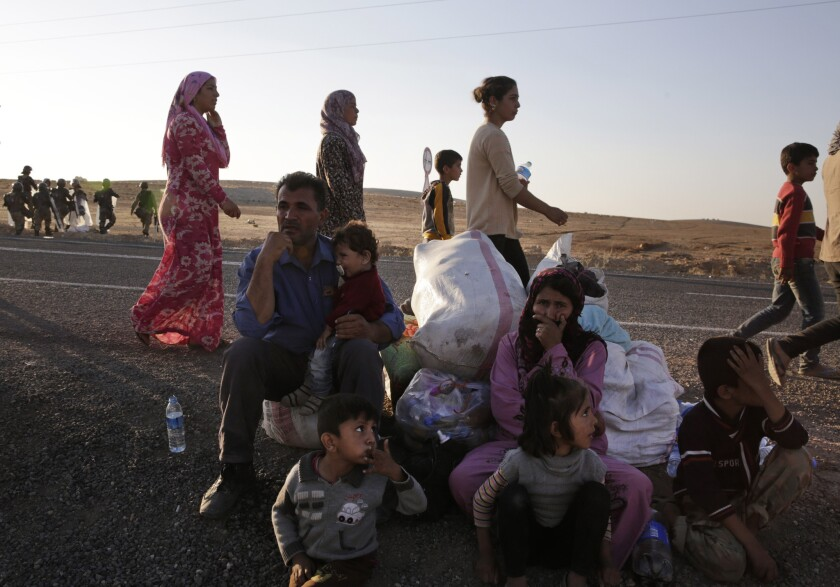 Kurdish refugees wait by the side of the road Oct. 5 near Suruc, Turkey, after their arrival from Kobani, Syria. Fighting between Syrian Kurds and the militants of Islamic State has intensified in Kobani.