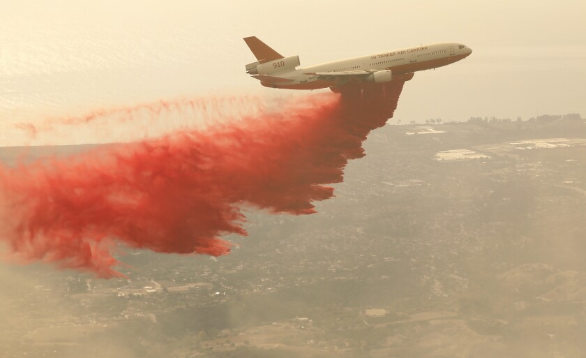 An air tanker drops fire retardant on the Cave fire