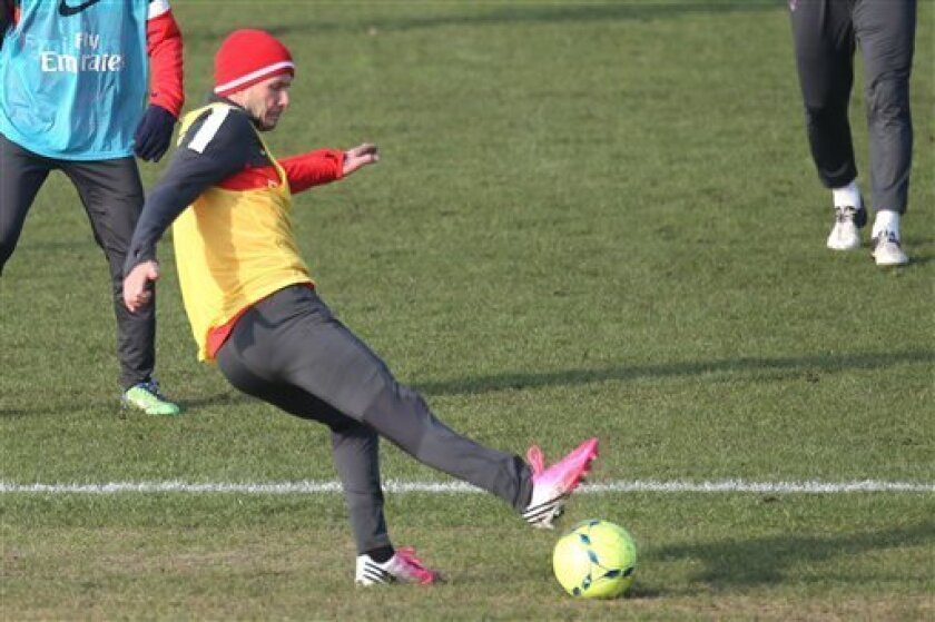 David Beckham kicks the ball during a practice session with Paris Saint-Germain soccer team in Saint-Germain-en-Laye, west of Paris, Wednesday, Feb. 13, 2013. David Beckham started his first practice session with Paris Saint-Germain on Wednesday amid a media frenzy as dozens of camera crews and pho