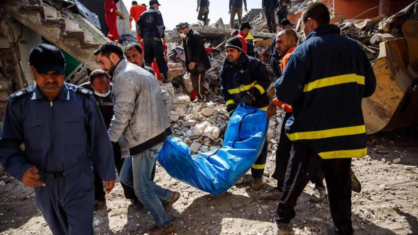 With the help of family members, Iraqi civil defense force members on March 24, 2017, recover a body buried in the rubble of a home destroyed by airstrikes in the Jadidah neighborhood of Mosul.
