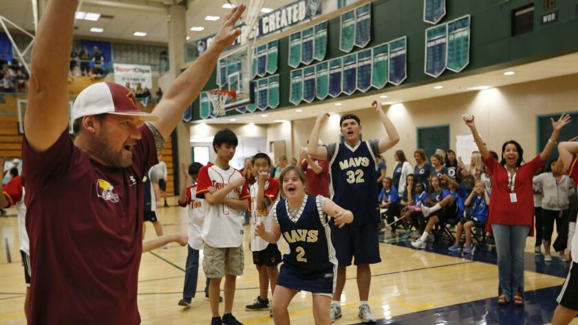LCC's Bridget Cuneo (2) is delighted after making a basket. Cheering at left is Torrey Pines special education teacher Ryland Wickman.