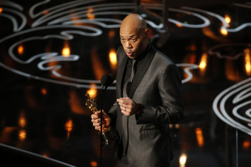 "John Ridley accepting his Oscar for adapted screenplay for ""12 Years a Slave."""