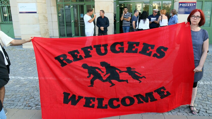 Migrant supporters hold a banner in front of the police station in Eisenstadt, Austria, on Thursday.