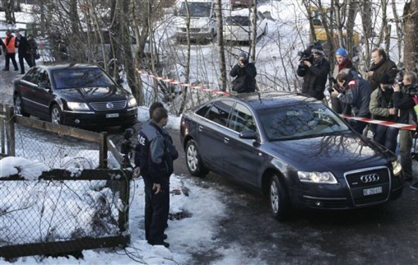 Swiss police drive a car, right, with Roman Polanski inside on the access road to the film director's chalet in Gstaad, Switzerland, Friday, Dec. 4, 2009. Roman Polanski's family waited inside the director's Alpine chalet Friday as Swiss authorities worked out the last-minute details of his transfer to house arrest. (AP Photo/Anja Niedringhaus)