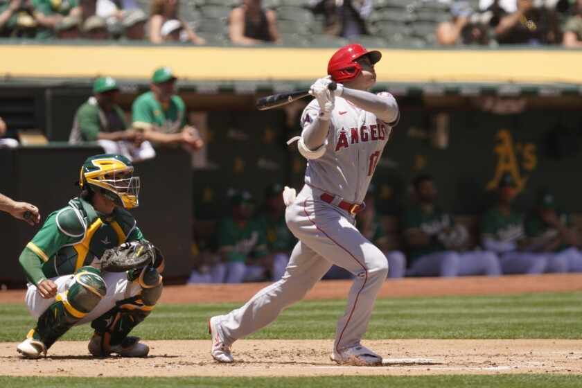 Los Angeles Angels' Shohei Ohtani hits a home run in the second inning of a baseball game Wednesday, June 16, 2021, in Oakland, Calif. Looking on is Athletics catcher Aramis Garcia. (AP Photo/Eric Risberg)