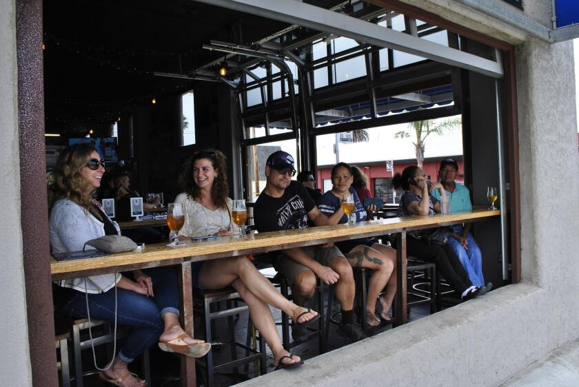 A seat on the open-window patio is in-demand on a Saturday afternoon at Mike Hess Brewing.