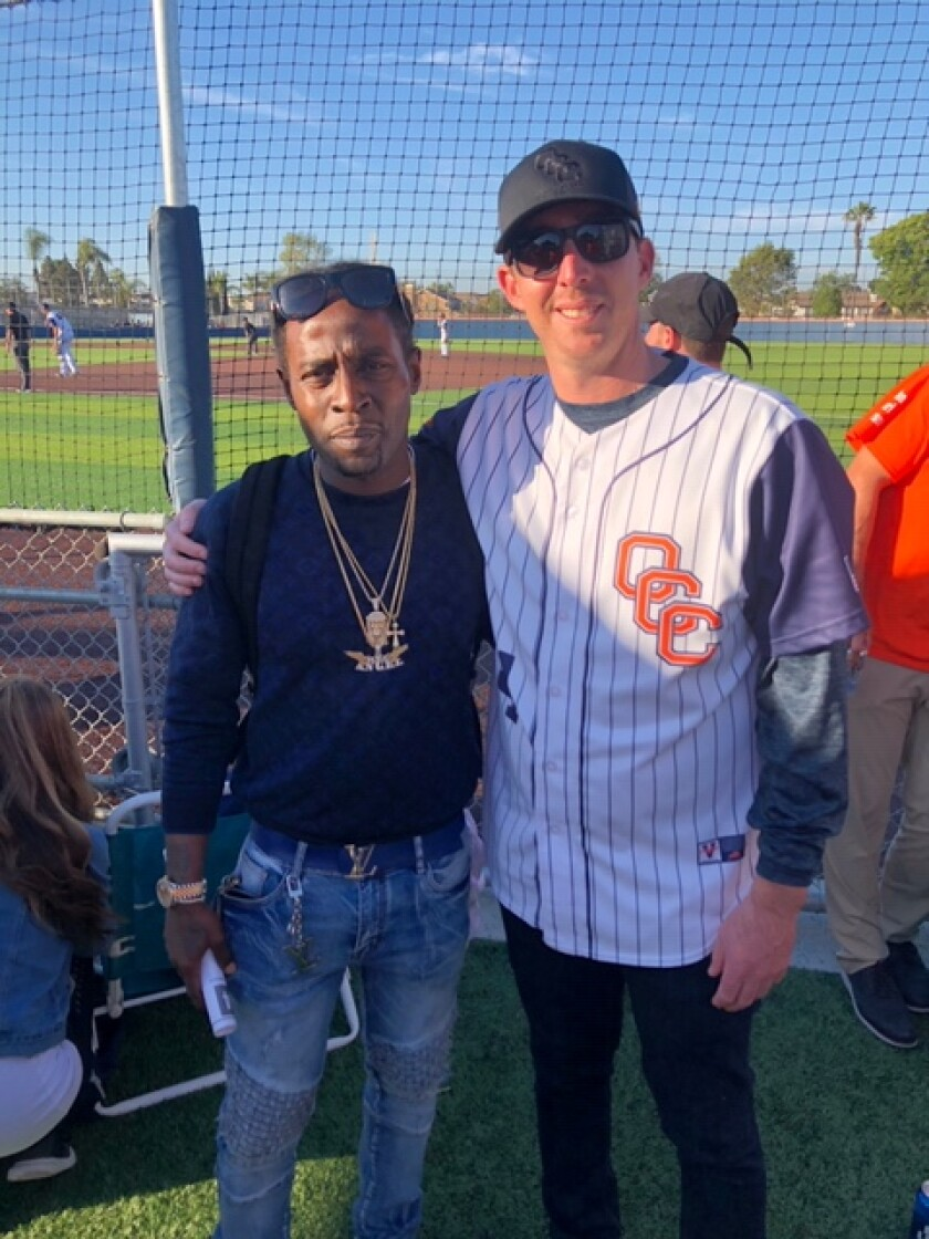 Former Orange Coast College baseball player LaBarian Willis and J.J. Altobelli pose for a photograph at Tuesday's game.
