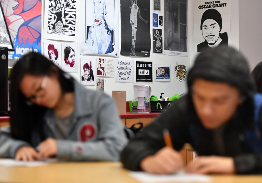 A female and male high school student, out of focus, work at desks in front of posters featuring Black Lives Matter, Oscar Grant, a Golden State Warrior and more.
