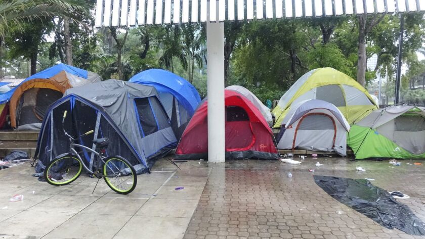 Rain pours down on the tents at the homeless encampment in front of the Broward County Main Library