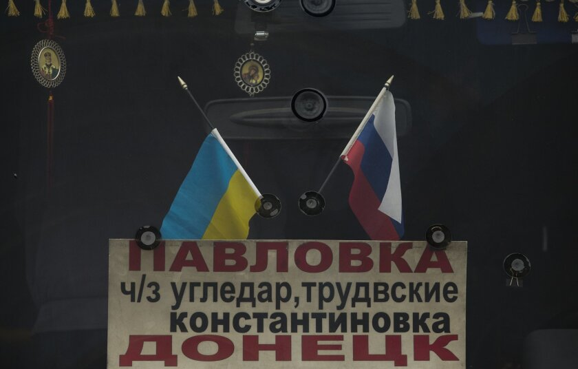 In this photo taken Tuesday, Feb. 25, 2014, the Russian and Ukrainians flags decorate windshield of a bus, in Donetsk, eastern Ukraine. If Ukraine looks neatly delineated on maps, its history is a tangle of invasions and occupations and peoples and religions, a place of ill-defined borders that for