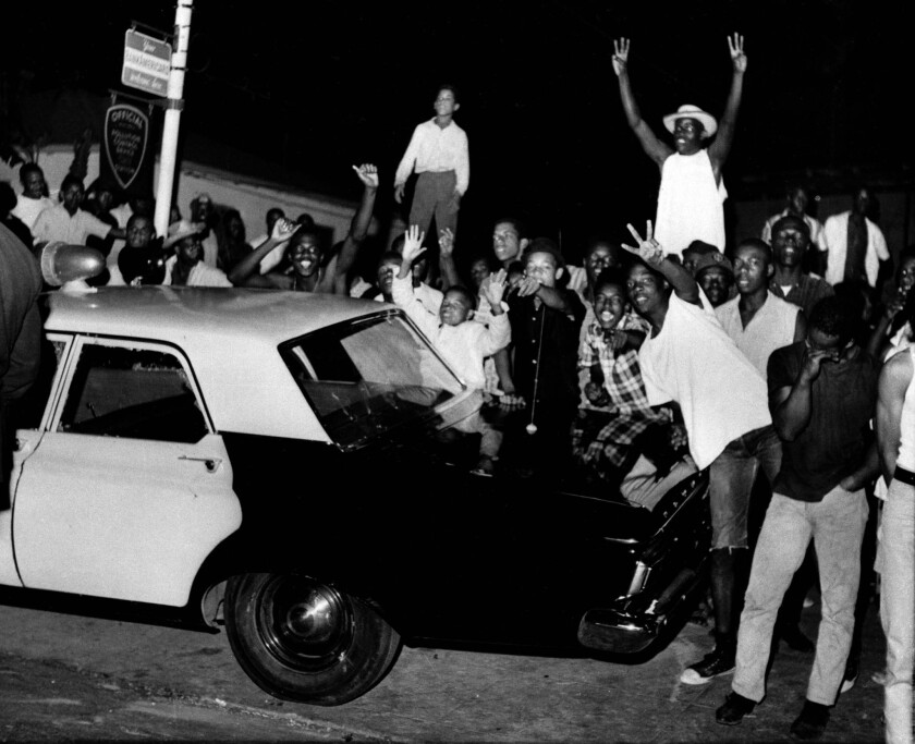 Demonstrators push against a police car during riots in Watts on Aug. 12, 1965.