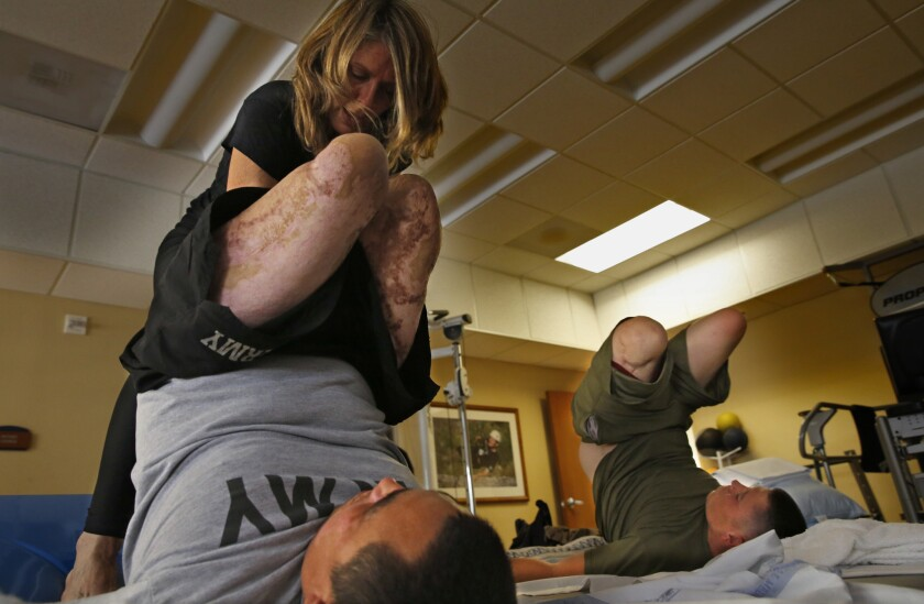 Yoga instructor Sunny Keays works with Army 1st Sgt. Chris Montera, left, and Marine Pfc. Isaac Blunt at the Naval Medical Center San Diego.