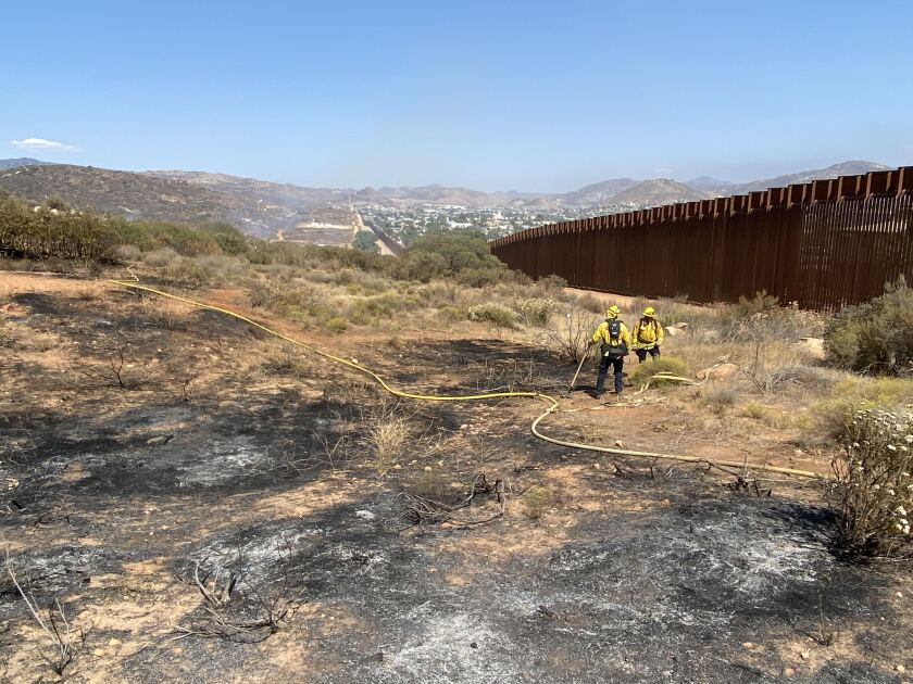 Cal Fire San Diego firefighters deal with a brushfire Thursday afternoon near the Tecate Port of Entry.